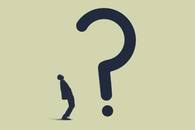 Businessman looking up at large question mark
